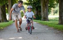 Pai ensinando filho andar bicicleta capa